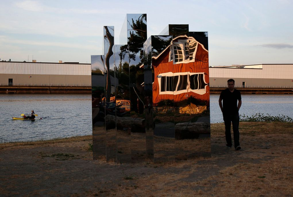 """Sculpture artist Ben Zamora is shown with his piece titled """"Alone. Standing in the Middle of Darkness. Invisible.,"""" a sculpture that is part of the """"Duwamish Revealed"""" project. (Sy Bean/The Seattle Times)"""