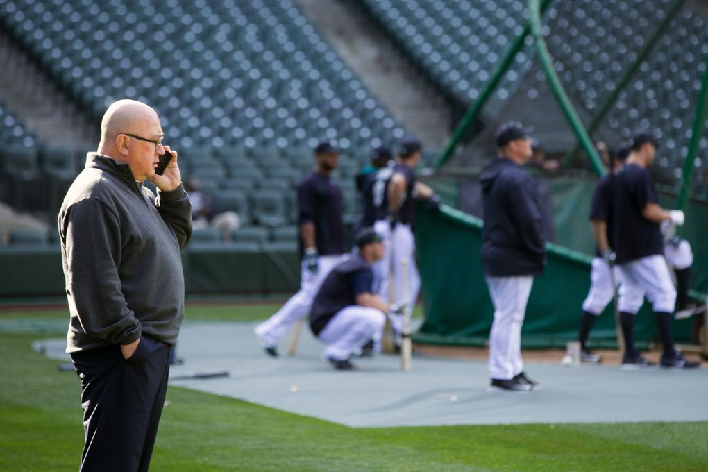 Mariners general manager Jack Zduriencik talks on the phone as the Seattle Mariners warm up to take on the Houston Astros at Safeco Field in Seattle Wednesday April 22, 2015. (Bettina Hansen / The Seattle Times)