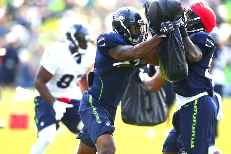 Seattle Seahawks linebacker Eric Pinkins, left, works out with teammate Tyrell Adams during training camp. (John Lok / The Seattle Times)