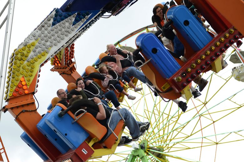 """Fair attendees brave the """"Nitro"""" ride, a large whirling pendulum, at the carnival grounds at the Evergreen State Fair in Monroe, Snohomish County. The fair runs Aug. 27-Sept. 7. (Lindsey Wasson / The Seattle Times)"""
