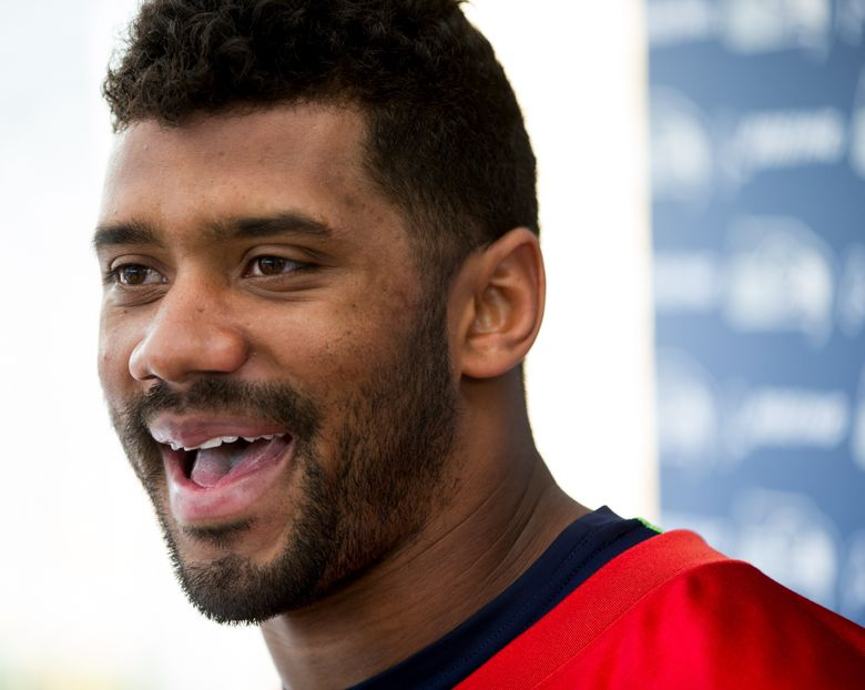 Seahawks quarterback Russell Wilson talks about Reliant Recovery Water after practice Thursday. (MIke Siegel/The Seattle Times)