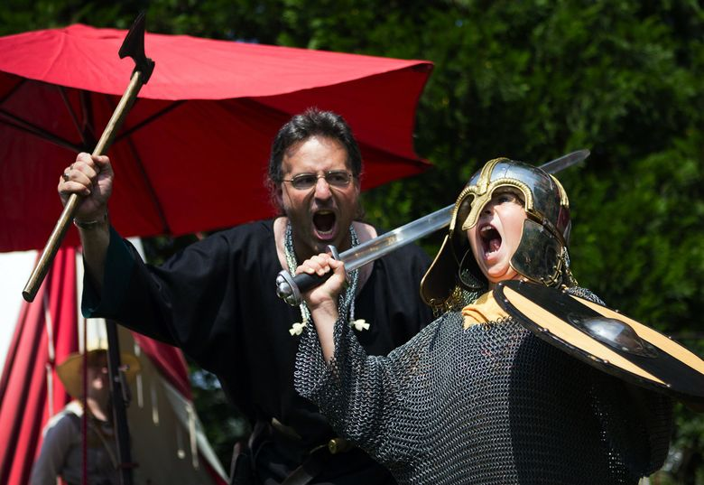 Henry Durand, right, and volunteer Eugene Ulrich unleash mighty battle cries at last year's Viking Days. This year's festival is Saturday and Sunday, Aug. 22-23.  (LINDSEY WASSON/The Seattle Times )