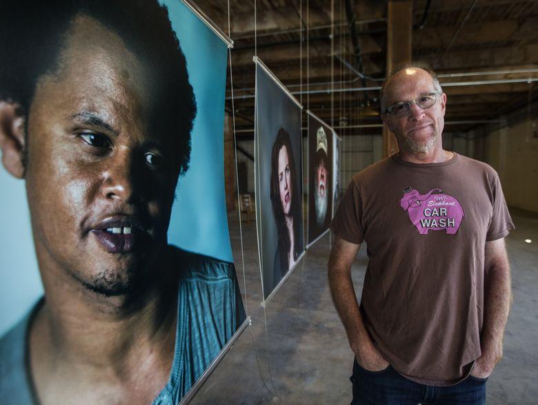 Photographer Ernie Sapiro stands next to his portrait of jazz musician Evan Flory-Barnes. (Steve Ringman/The Seattle Times)