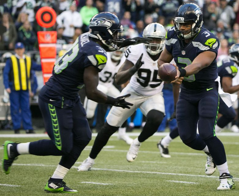 Seahawks quarterback Russell Wilson hands the ball to Seahawks running back Christine Michael in the first quarter. (Bettina Hansen / The Seattle Times)