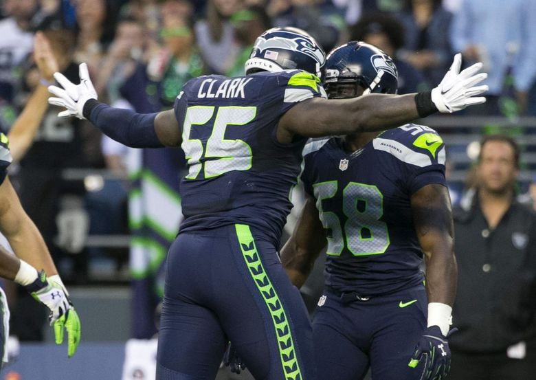Seahawks defensive lineman Frank Clark and Seahawks linebacker Kevin Pierre-Louis celebrate a tackle for a loss in the first quarter as the Seahawks take on the Oakland Raiders for the fourth preseason game Thursday at CenturyLink FIeld. (Bettina Hansen / The Seattle Times)
