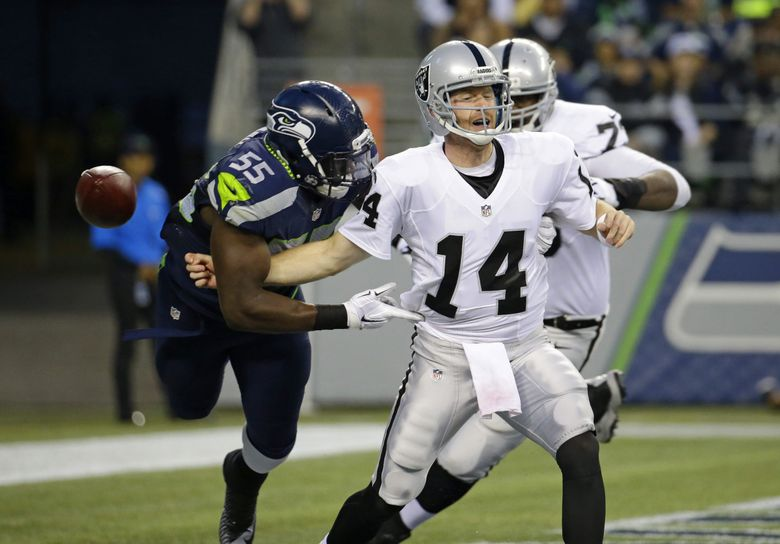 Seattle Seahawks defensive end Frank Clark (55) causes Oakland Raiders quarterback Matt McGloin (14) to fumble in the second quarter of a preseason NFL football game, Thursday, Sept. 3, 2015, in Seattle. defensive tackle Jordan Hill recovered the ball in the end zone for a touchdown. (Elaine Thompson / The Associated Press)