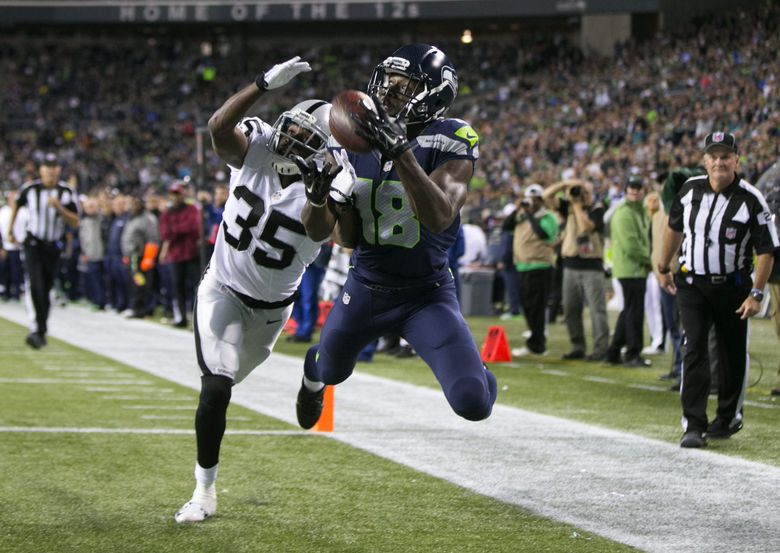 Seahawks wide receiver Kasen Williams catches a touchdown in front of Raiders cornerback Chimidi Chekwa in the third quarter Thursday at CenturyLink Field. (Bettina Hansen / The Seattle Times)