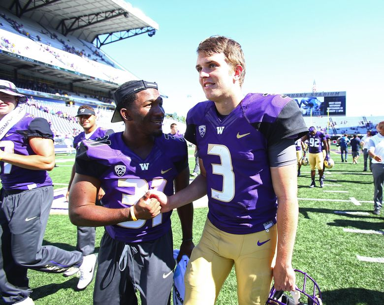 Washington quarterback Jake Browning, right, leaves the field after defeating the Sacramento State Hornets 49-0 at their home opener at Husky Stadium. (John Lok / The Seattle Times)