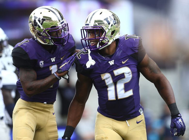 Washington tailback Dwayne Washington  (12) celebrates his touchdown with Washington wide receiver Jayden Mickens (1) in the first half of the game against the Utah State Aggies at Husky Stadium on Saturday.   (Lindsey Wasson / The Seattle Times)