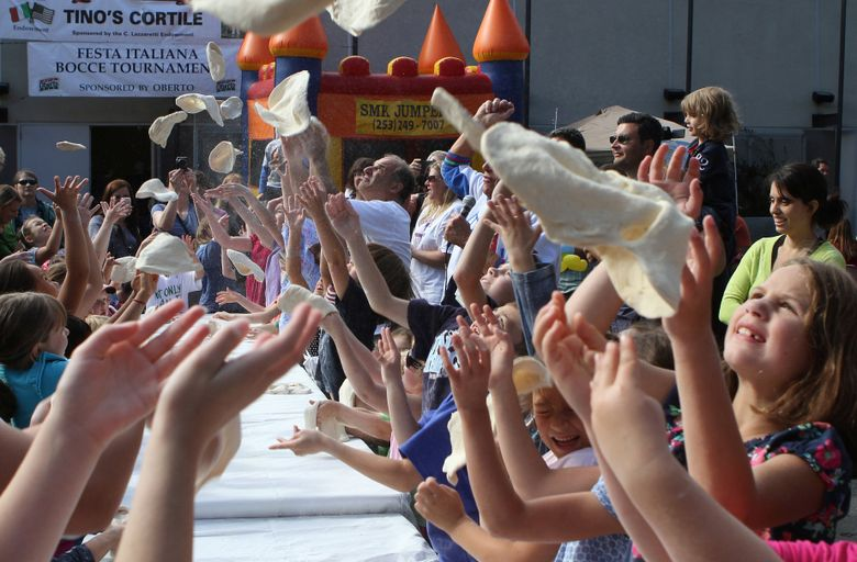 Children practice tossing pizza dough in the air at a past Festa Italiana at Seattle Center. This year's festival is Saturday and Sunday, Sept. 26-27. (Ellen M. Banner/The Seattle Times)