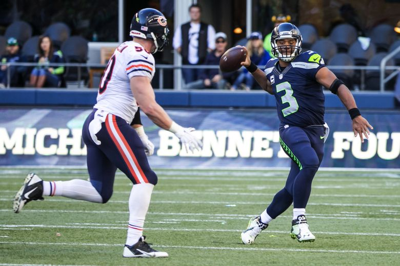 Seahawks quarterback Russell Wilson throws the ball away under pressure from Bears linebacker Shea McClellin on Sept. 27, 2015. The Seahawks shut out the Bears, 26-0. (Bettina Hansen / The Seattle Times)