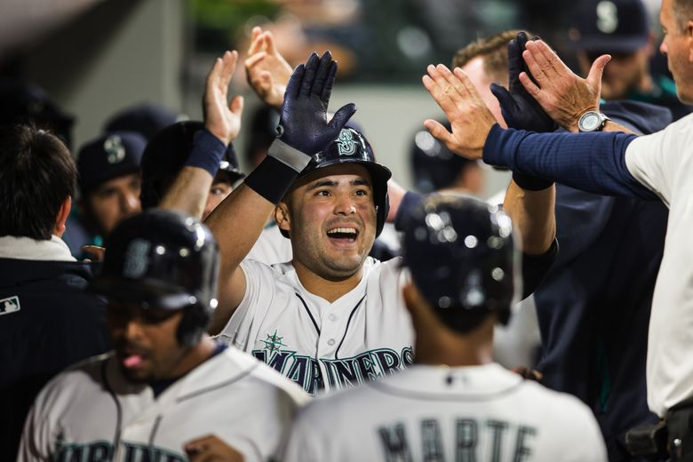 Jesus Montero is welcomed back into the Mariner dugout after hitting a 3-run homer in the fourth inning off LA starting pitcher Jered Weaver in a game in September, 2015.  (Dean Rutz/The Seattle Times)