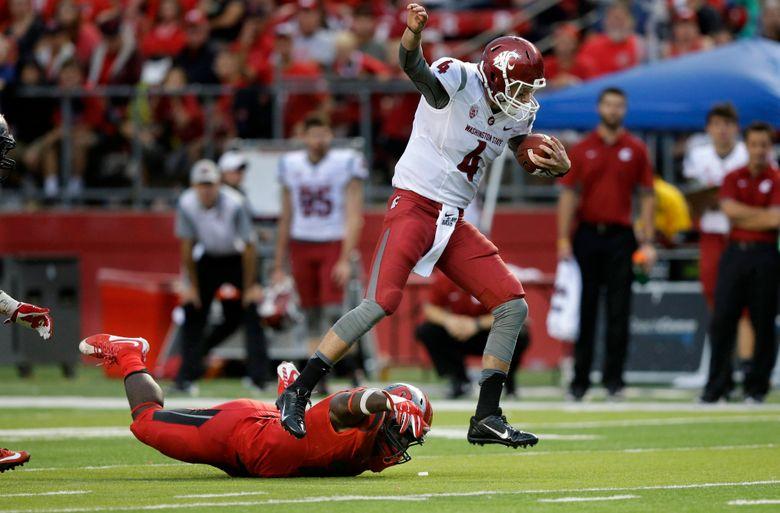 Washington State quarterback Luke Falk evades Rutgers defensive lineman Quanzell Lambert late in the second half of WSU's 37-34 win on Saturday.  (Mel Evans/AP)