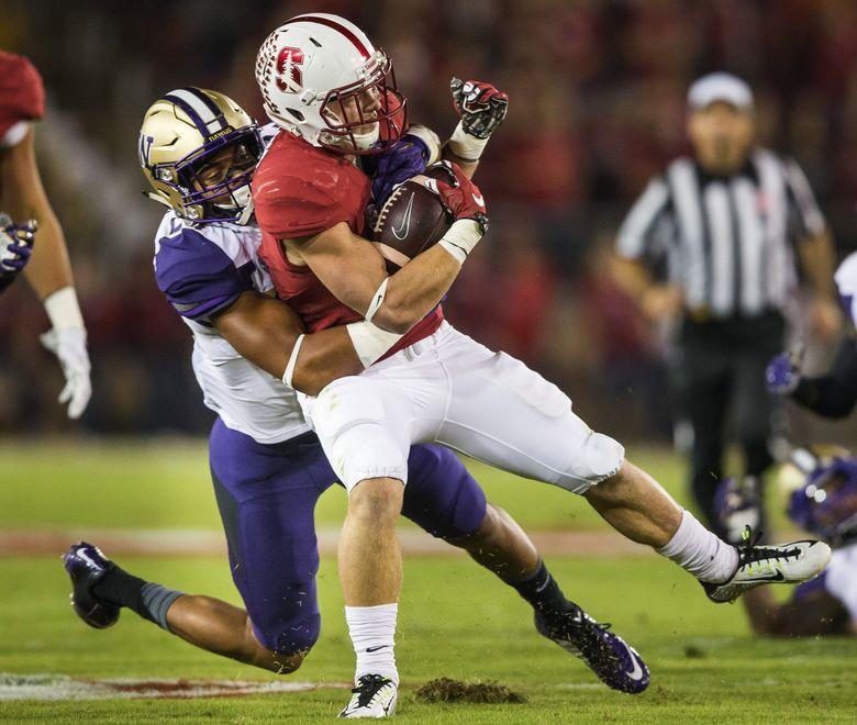 UW's Ezekiel Turner pulls down Stanford running back Christian McCaffrey after a 9-yard pickup. (Dean Rutz/The Seattle Times)