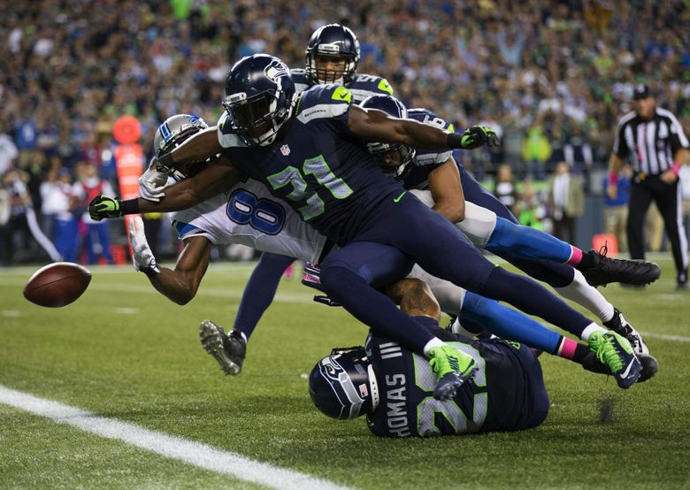 Seahawks safety Kam Chancellor punches the ball free from Lions wide receiver Calvin Johnson, sending it through the end zone for a touchback in the fourth quarter. (Dean Rutz / The Seattle Times)