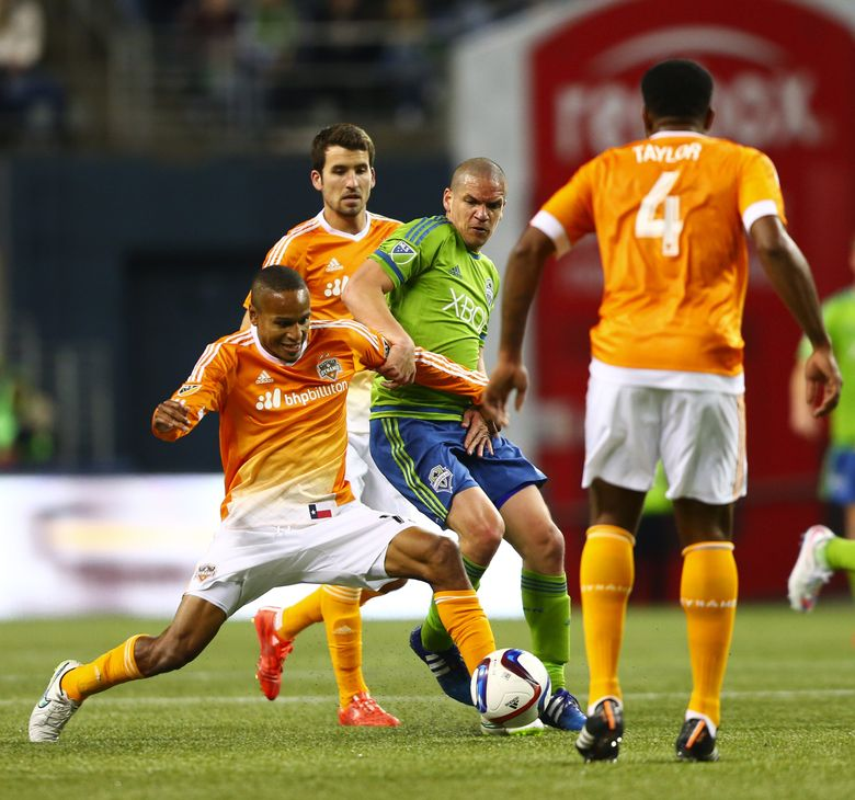 Sounders midfielder Osvaldo Alonso battles against Dynamo midfielder Ricardo Clark for the ball at mid-field in the second half of the game at CenturyLink Field on Saturday, April 4, 2015. The Sounders beat the Houston Dynamo, 1-0. This was Alonso's first appearance of the 2015 after returning from a groin injury.