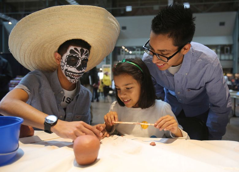 Daniel Miranda, left, helps his sister, Alondra, paint a clay skull as brother Omar watches at the Dia de Muertos celebration at Seattle Center in 2012.  (Colin Diltz/The Seattle Times)