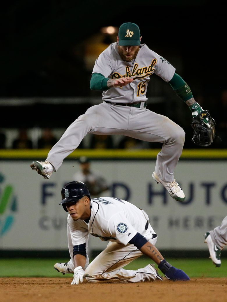 Oakland third baseman Brett Lawrie forces out shortstop Ketel Marte at second and throws to first for a double play ending the ninth inning. (Ted S. Warren/AP)
