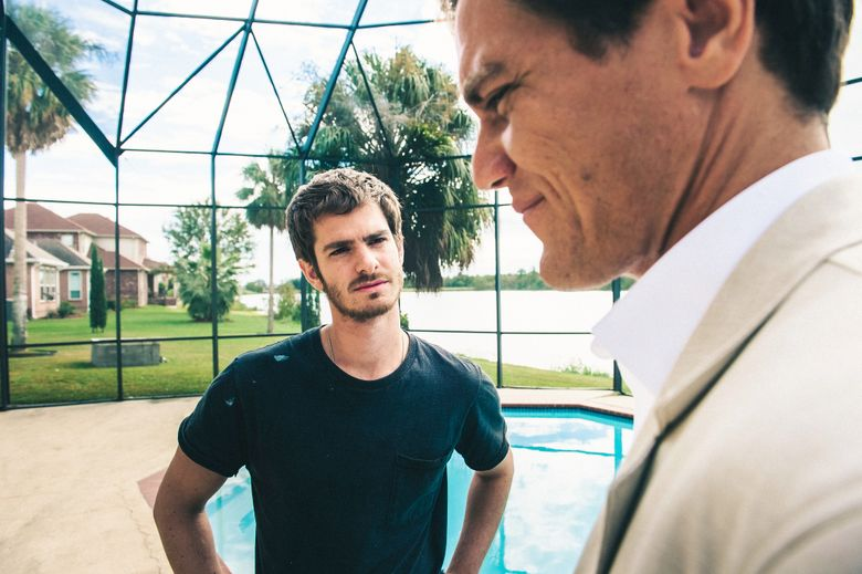 """A ruthless real-estate broker (Michael Shannon, right) manipulates a construction worker (Andrew Garfield) desperate to keep his house in """"99 Homes.""""  (Hooman Bahrani)"""