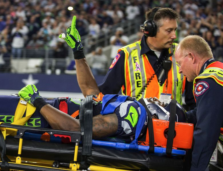 Ricardo Lockette holds up his hand to signify he is okay as he is taken off by medics Sunday. (Dean Rutz/The Seattle Times)
