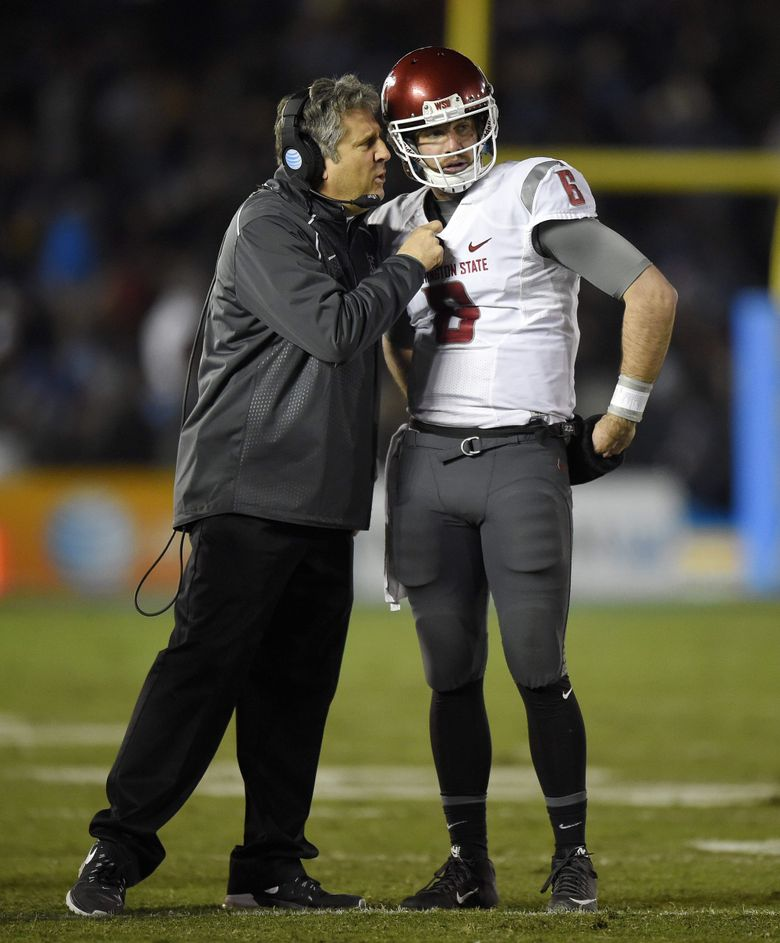 Washington State head coach Mike Leach, left, talks with quarterback Peyton Bender during the first half of an NCAA college football game against UCLA.  (Mark J. Terrill / The Associated Press)