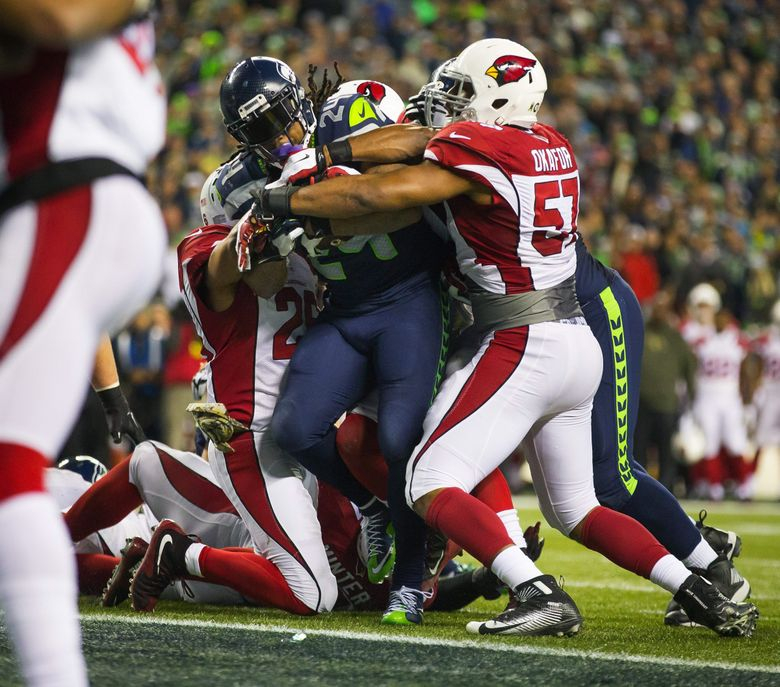 Seahawks running back Marshawn Lynch punches the ball in to the end zone for a 3-yard touchdown run during the fourth quarter Sunday against the Arizona Cardinals at CenturyLink Field.   (Dean Rutz / The Seattle Times)