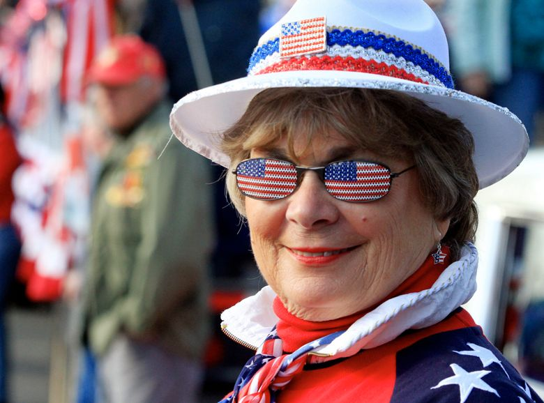 Loree Pickett wears the flag proudly as she watches the Veterans Day Parade in Auburn. This year's event takes place Saturday, Nov. 7.  (Alan Berner/The Seattle Times)