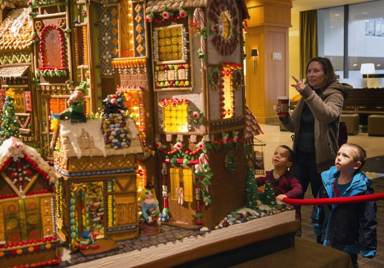 Jessica Rossman and her sons, Theo and Torben Berger, check out a gingerbread house at the Seattle Sheraton in 2013. This year's Gingerbread Village opens Tuesday, Nov. 24. (Ellen M. Banner/The Seattle Times)