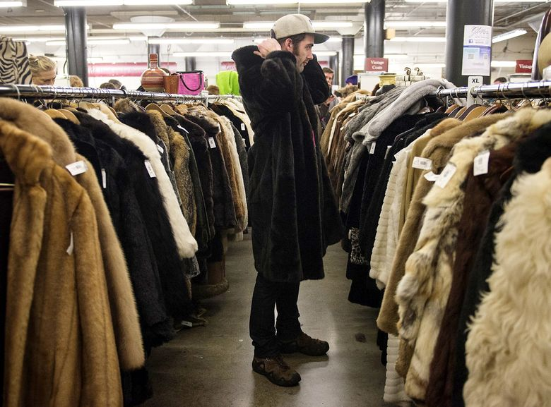 Conrad Ely tries on a fur coat during the annual Goodwill Glitter Sale. This year's event is Saturday and Sunday, Nov. 14-15.  (LINDSEY WASSON/The Seattle Times)
