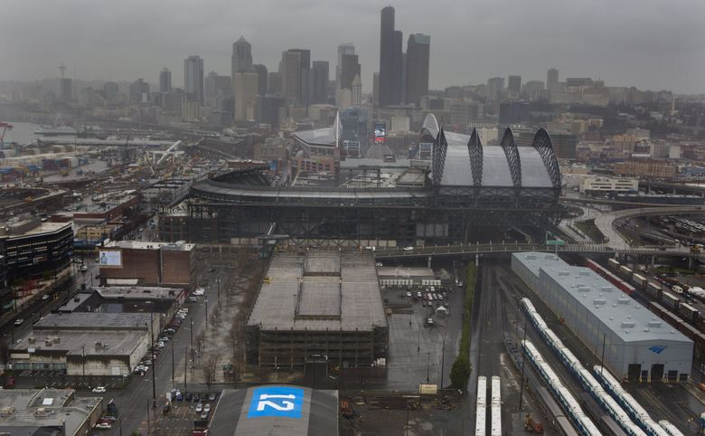 """John Phillips and others, with the blessing of Chris Hansen they say, painted a 50×70 foot """"12"""" flag on the roof of a building at the site of the proposed NHL/NBA arena in Seattle's Sodo neighborhood. (Ellen M. Banner/The Seattle Times)"""