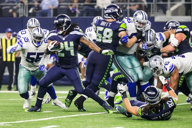 Marshawn Lynch (24) again was a workhorse for Seattle, gaining 7 yards here in the third quarter and 71 yards on 21 carries for the game Sunday against Dallas. (Bettina Hansen/The Seattle Times)