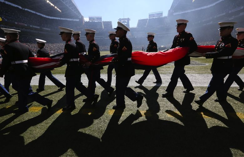 The Marine honor guard from Bangor leaves the field after the national anthem for the Seahawks' home opener against Chicago in September. (Alan Berner/The Seattle Times)