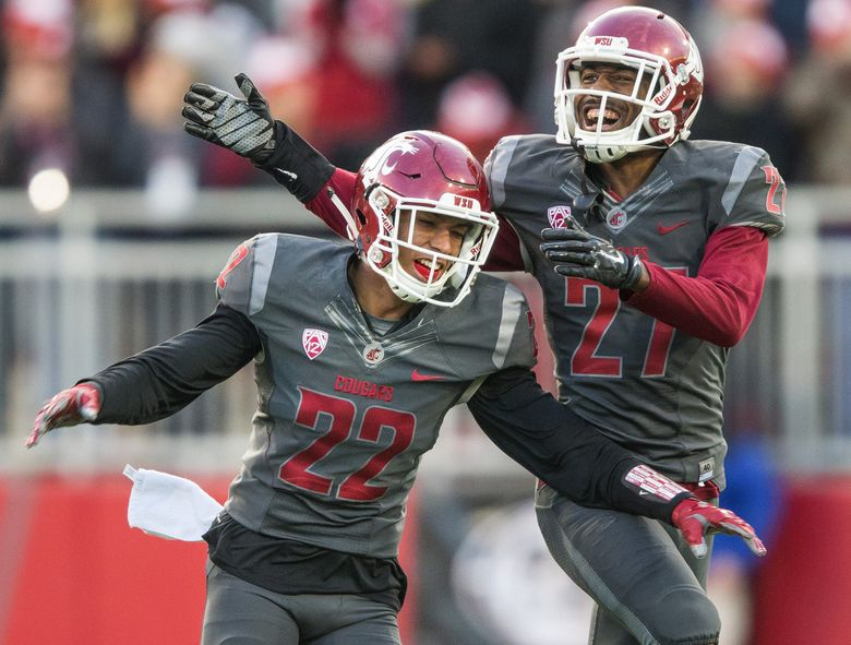 Cornerback Darrien Molton (22) is congratulated by Marcellus Pippins after his second-half interception. (Dean Rutz/The Seattle Times)