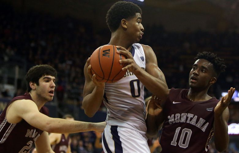 Washington's Marquese Chriss (0) keeps the ball away from Montana's Michael Oguine (10).  (Sy Bean / The Seattle Times)