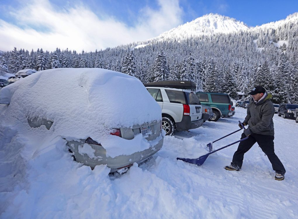 Tyler Meyers of Tacoma digs out his car at Crystal Mountain parking lot. Skiing has been tremendous this winter with lots of powder every day.  (Steve Ringman / The Seattle Times)