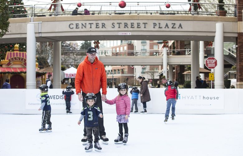 Andrew Newell, center, skates with his children Mayes and Sawyer at a synthetic ice rink at Redmond Town Center in 2014. (LINDSEY WASSON/THE SEATTLE TIMES)