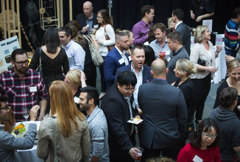 Dozens of young professionals mingle during an Innovators Network happy-hour event at the Fred Hutchinson Cancer Research Center. The group is aimed at young professionals to help raise money for funding early-stage research. (Lindsey Wasson / The Seattle Times)