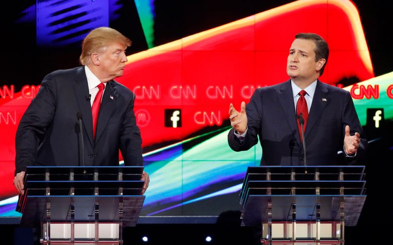 In this Dec. 15, 2015 photo, Donald Trump, left, watches as Ted Cruz speaks during the CNN Republican presidential debate at the Venetian Hotel & Casino in Las Vegas. A growing debate over America's role in promoting regime change in the Middle East is creating unusual alliances among 2016 presidential candidates that cross party lines.  (AP Photo/John Locher)
