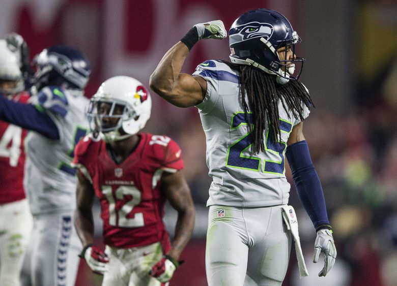 After knocking down a pass, Richard Sherman flexes his muscle toward the Cardinals bench in the fourth quarter. (Dean Rutz / The Seattle Times)