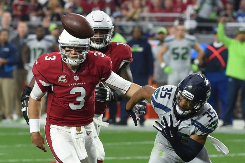 Cardinals QB Carson Palmer looks at the football after Seahawks defensive back DeShawn Shead deflected a pass in the first half Sunday in Glendale, Ariz. (Norm Hall / Getty Images)