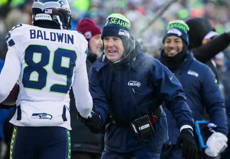 Seahawks head coach Pete Carroll congratulates wide receiver Doug Baldwin for his touchdown in the third quarter Sunday in Minneapolis. (Bettina Hansen / The Seattle Times)