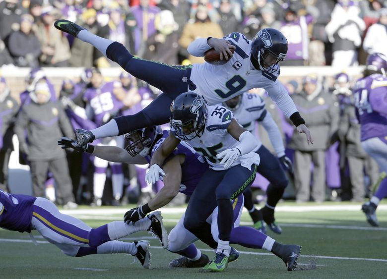 Seahawks punter Jon Ryan (9) jumps over Vikings linebacker Casey Matthews (59) as he runs the ball after a bad snap in the first quarter Sunday in Minneapolis. (Nam Y. Huh / The Associated Press)