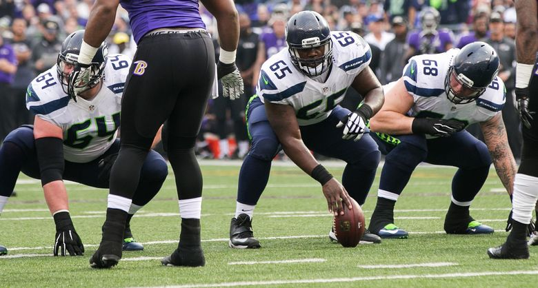 Seahawks offensive linemen J.R. Sweezy (left), Patrick Lewis (center) and Justin Britt prepare for Lewis' snap against the Ravens.  (Bettina Hansen/The Seattle Times)