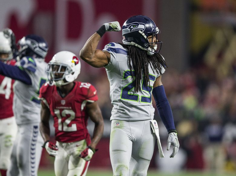 After knocking down a pass, Richard Sherman flexes his muscle toward the Cardinals in a game in January. (Dean Rutz / The Seattle Times)