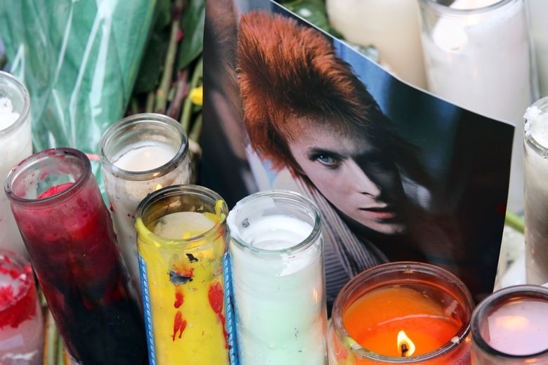 Candles and and a photograph are part of a make shift memorial outside the apartment building, Tuesday, Jan. 12, 2016, in New York, where David Bowie lived. Bowie, the chameleon-like star who transformed the sound – and the look – of rock with his audacious creativity and his sexually ambiguous makeup and costumes, died of cancer Sunday, Jan. 10.  (AP Photo/Mary Altaffer)