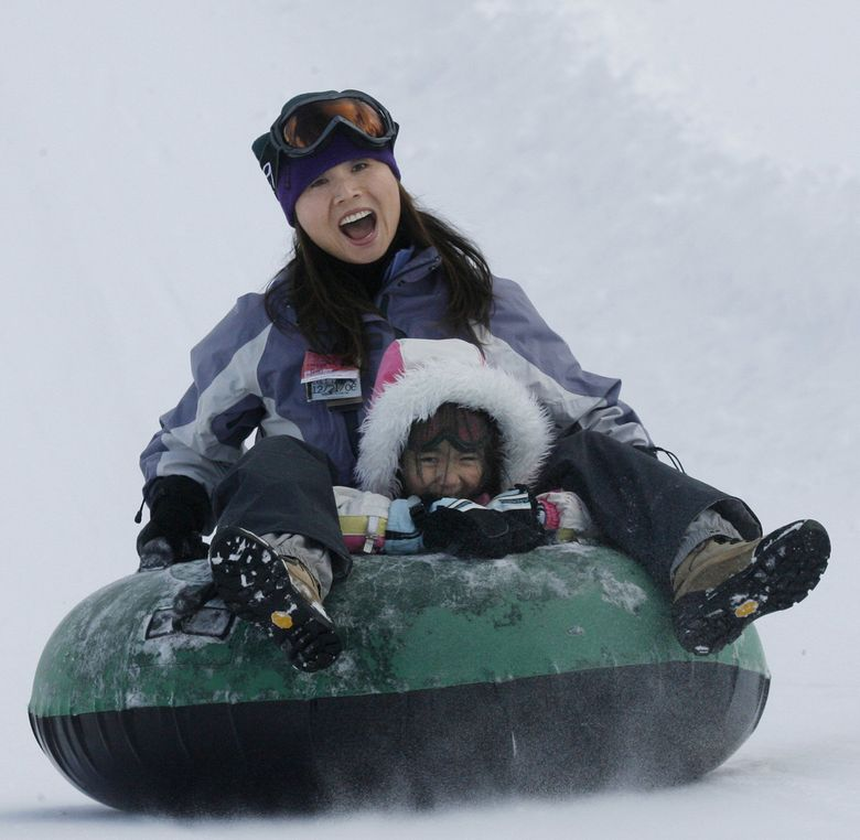 Tracy Unoki and daughter Elisa glide down the inner-tube run at the Summit at Snoqualmie Tubing Center. Advance registration is available for two-hour sessions four times daily on weekends and some weekdays.  (Alan Berner/The Seattle Times)