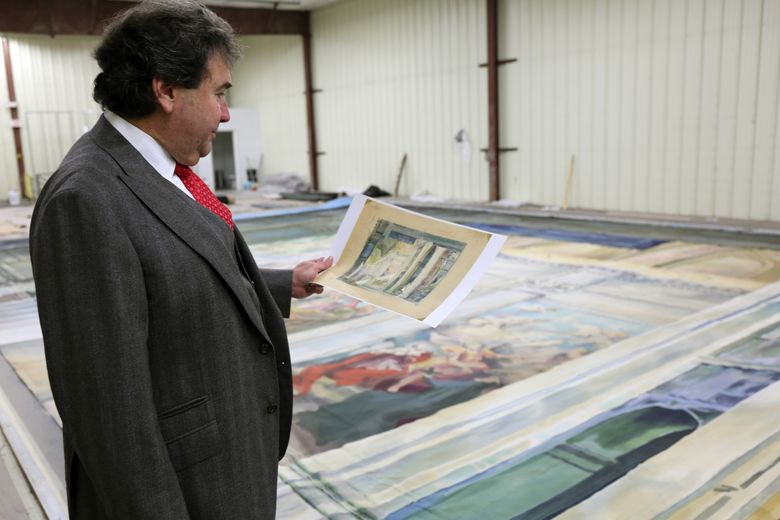 """In this undated image released by NYC Opera Renaissance, Michael Capasso, who will lead the reborn New York City Opera, examines drawings used for sets and costumes at the 1900 premiere of Puccini's """"Tosca"""" in Rome. The backdrops on the floor are being prepared for a recreated production at New York City Opera on Jan. 20-24. (John Farrell/NYCO Renaissance via AP)"""