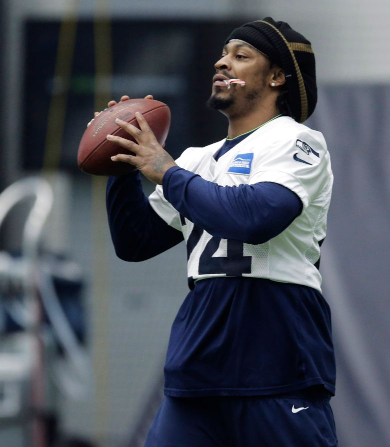 Seattle Seahawks running back Marshawn Lynch holds a candy cane in his mouth as he warms up before NFL football practice, Wednesday, Jan. 6, 2016, in Renton, Wash. Lynch has been recovering since having abdominal surgery last November. (AP Photo/Ted S. Warren)