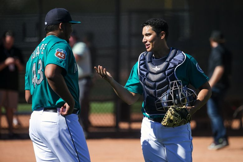 Pitcher Mayckol Guiape talks with catcher Steven Baron after throwing in the bullpen at Seattle Mariners spring training.  (Bettina Hansen / The Seattle Times)