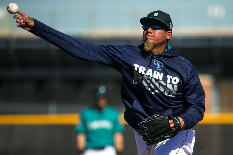 Pitcher Felix Hernandez throws off the mound during infield drills on Feb. 26 in Peoria, Ariz.  (Bettina Hansen / The Seattle Times)